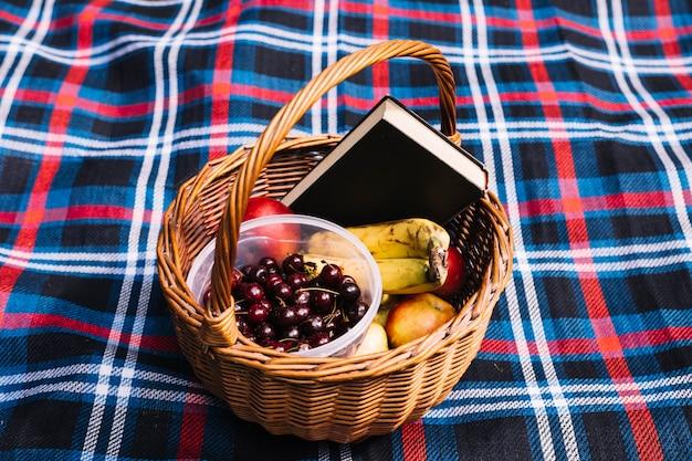 Cerejas; frutas e livro na cesta no cobertor