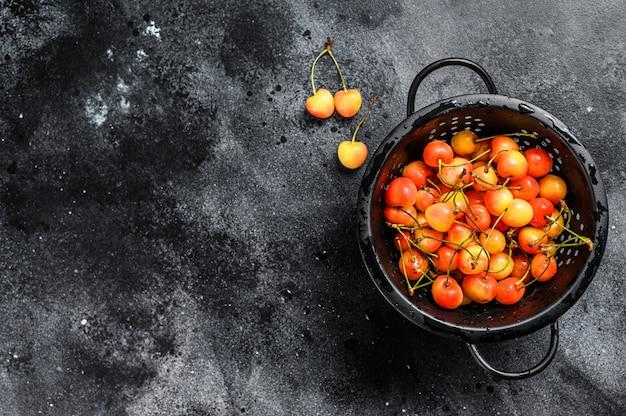 Cerejas maduras amarelas em uma peneira na mesa preta