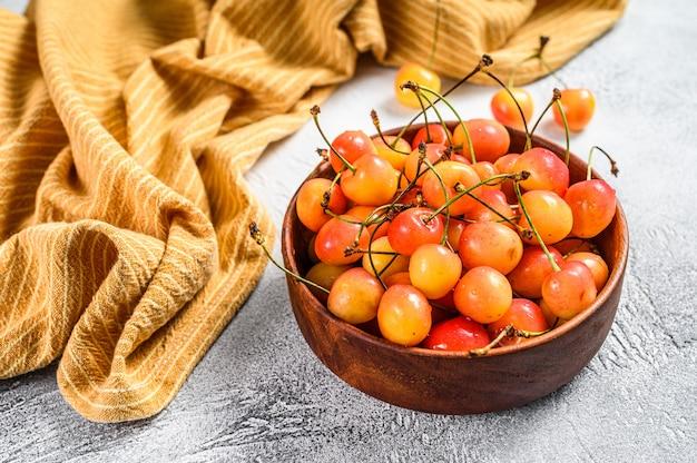 Cerejas maduras amarelas em uma tigela na mesa branca.