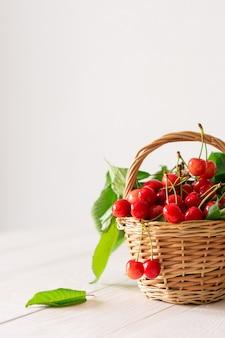 Cerejas maduras e suculentas em uma cesta de vime em um fundo branco de madeira