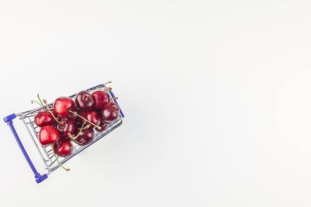 Cerejas maduras em um carrinho de compras isolado