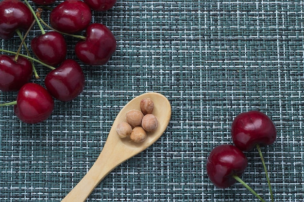 Cerejas maduras em um fundo de vime e uma colher de pau de baixo com miolo de bagas