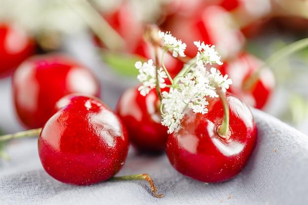 Cerejas maduras fica em um fundo branco de madeira