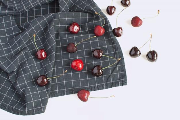 Cerejas maduras frescas em guardanapo xadrez branco backgroud