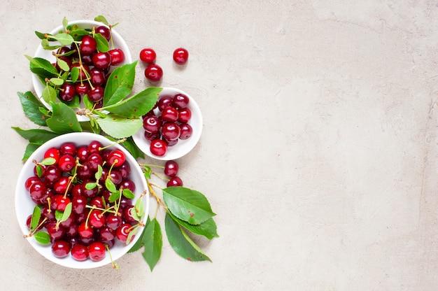 Cerejas maduras frescas nas placas brancas
