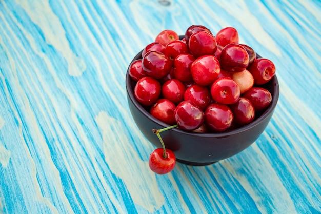 Cerejas maduras no espaço de cópia de fundo azul de madeira Foto Premium
