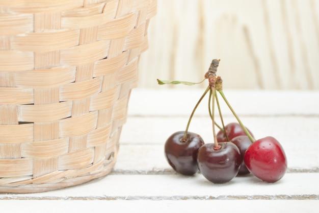 Cerejas maduras perto de uma cesta de vime. fechar-se