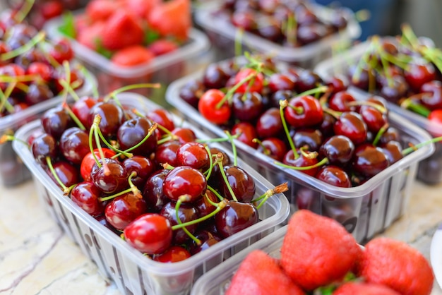 Cerejas maduras pretas e morango em caixa de plástico