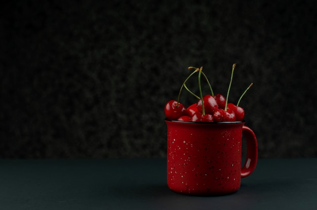 Cerejas na mesa de madeira com gotas de água