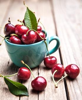 Cerejas na taça turquesa linda na mesa de madeira, macro, frutas, bagas
