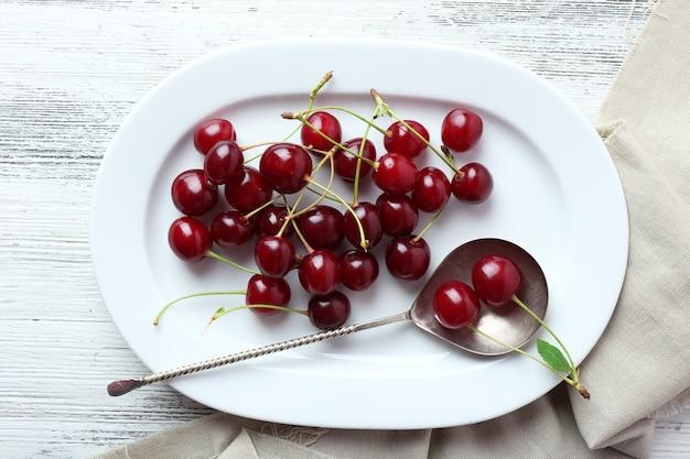Cerejas no prato na mesa de madeira