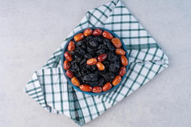 Cerejas pretas secas e frutas jujuba em uma travessa na superfície do concreto.