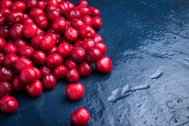 Cerejas recém colhidas com gotas de orvalho e água em um fundo de pedra azul escuro. o conceito de colheita. vista plana, vista superior