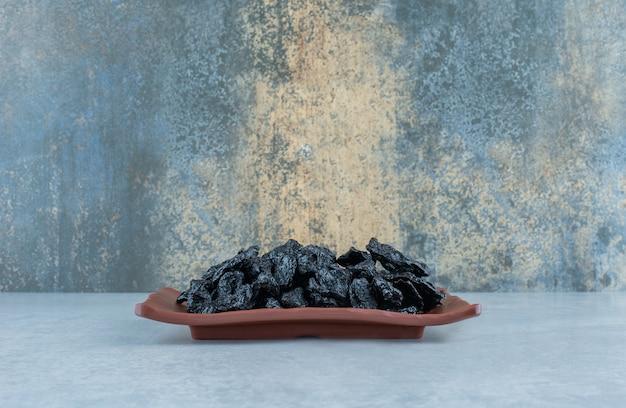 Cerejas secas em uma bandeja de madeira sobre fundo azul. foto de alta qualidade