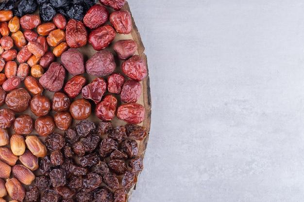 Cerejas secas, frutas vermelhas e tâmaras em uma bandeja de madeira. foto de alta qualidade