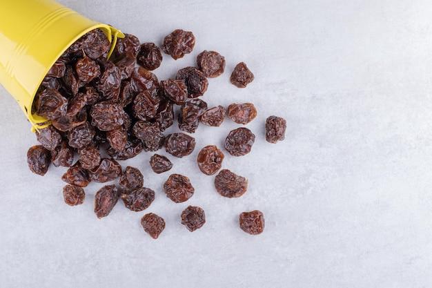 Cerejas secas marrons dentro de um prato com fundo de concreto. foto de alta qualidade