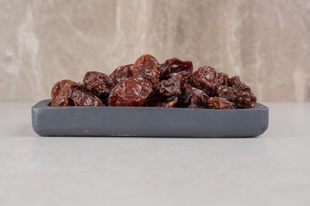 Cerejas secas marrons em uma bandeja de madeira.