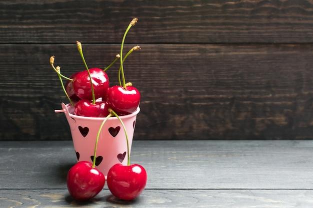 Cerejas selecionadas maduras em um pequeno balde de ferro-de-rosa sobre um fundo de madeira