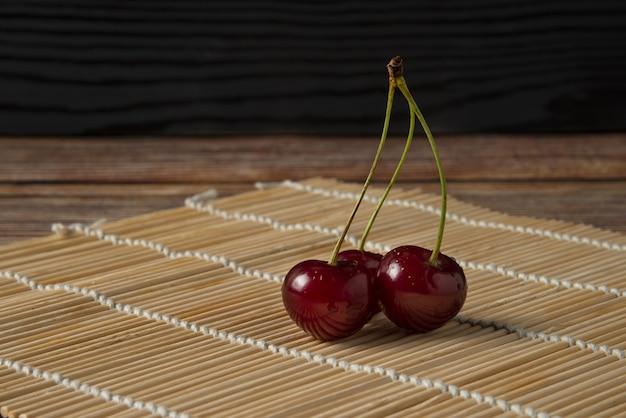 Cerejas vermelhas com hastes verdes no fosco rústico