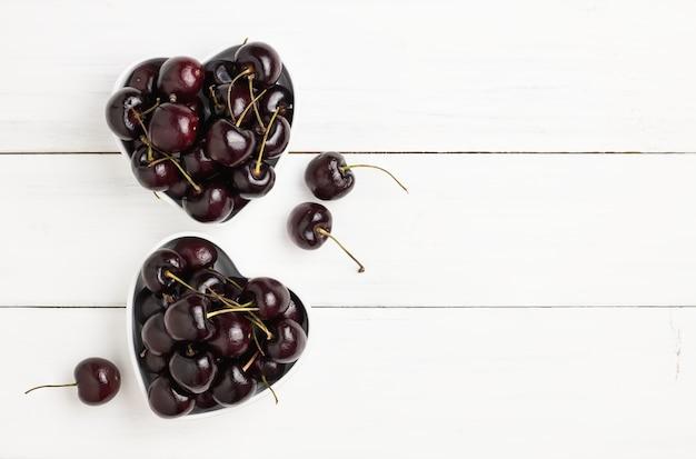Cerejas vermelhas e pretas maduras frescas na bacia dois coração-dada forma no assoalho de madeira branco da prancha.