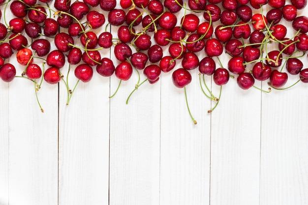 Cerejas vermelhas em madeira branca