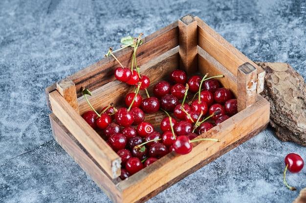 Cerejas vermelhas frescas e suculentas em uma caixa de madeira com folhas