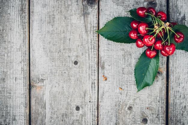 Cerejas vermelhas frescas em uma velha mesa de madeira com folhas verdes, estilo rústico.