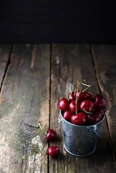 Cerejas vermelhas frescas na mesa de madeira com gotas de água