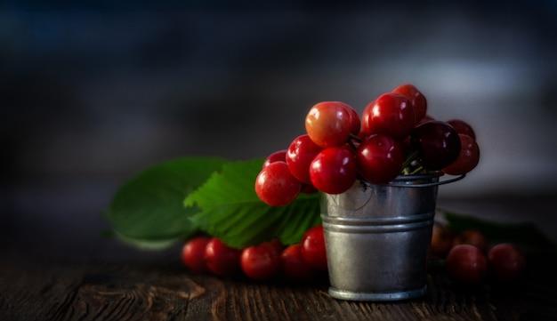 Cerejas vermelhas frescas no pequeno balde de metal na mesa de madeira velha