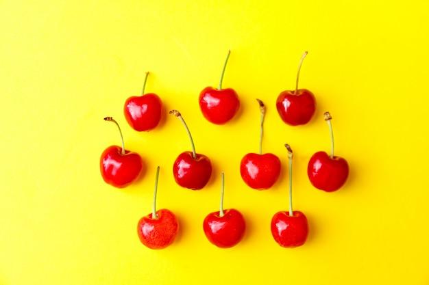 Cerejas vermelhas frescas sobre fundo amarelo, propaganda, cartaz.
