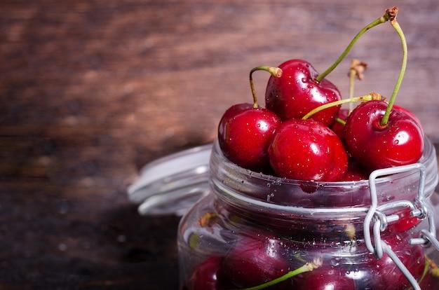 Cerejas vermelhas grandes em um frasco de vidro no fundo de madeira escuro com espaço da cópia.