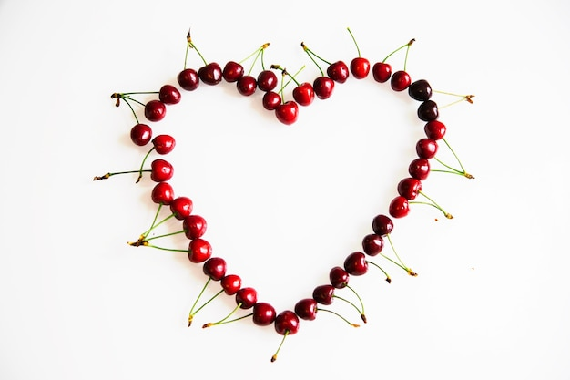 Cerejas vermelhas maduras dispostas na forma de um coração em um dia de background.valentine branco.