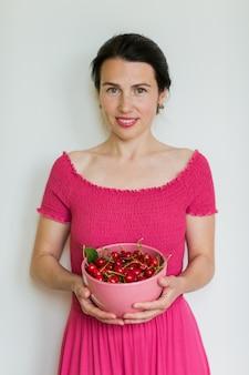 Cerejas vermelhas maduras em uma tigela nas mãos da mulher. alimentação saudável, comida vegetariana e conceito de dieta de pessoas