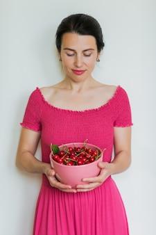 Cerejas vermelhas maduras em uma tigela nas mãos de uma mulher saudável comendo conceito de comida vegetariana