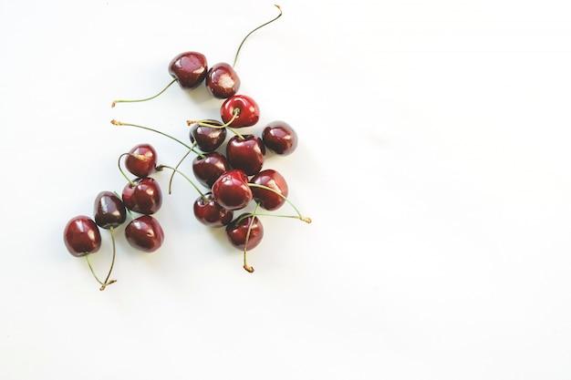 Cerejas vermelhas maduras. estilo leigo plano. dieta colorida e conceito de comida saudável.
