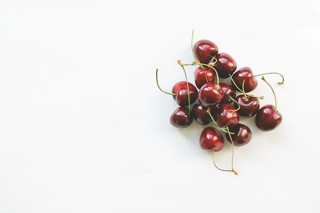 Cerejas vermelhas maduras. estilo leigo plano. dieta e conceito de comida saudável.