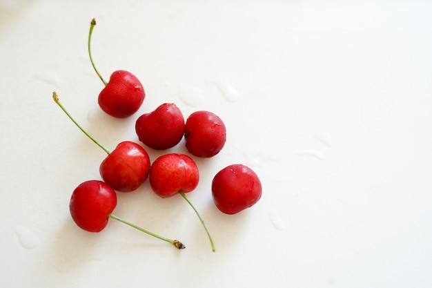 Cerejas vermelhas na mesa branca com espaço de cópia.