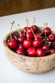 Cerejas vermelhas na tigela de madeira