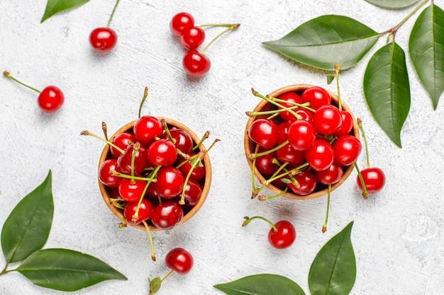 Cerejas vermelhas na tigela de prato na mesa cinza