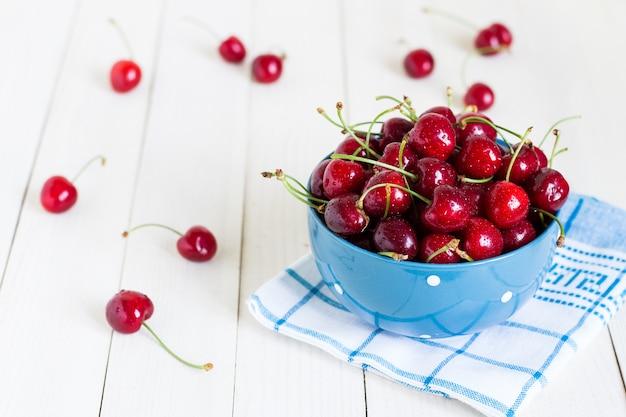 Cerejas vermelhas na tigela em madeira branca na toalha azul