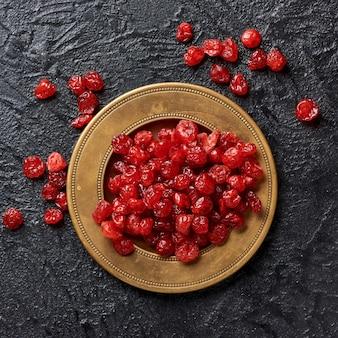 Cerejas vermelhas secas em um prato. vista do topo.
