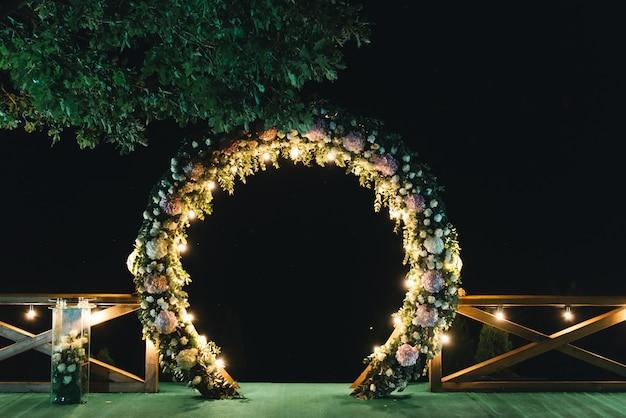 Cerimônia de casamento à noite. casamento é decorado com um arco à noite