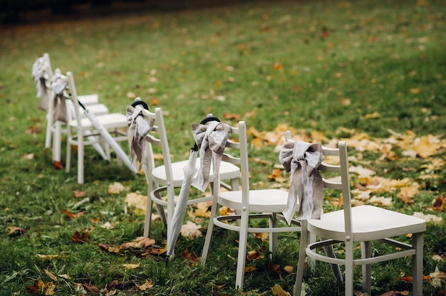 Cerimônia de casamento de outono na rua no gramado verde. decoração com arcos de flores frescas para a cerimônia.