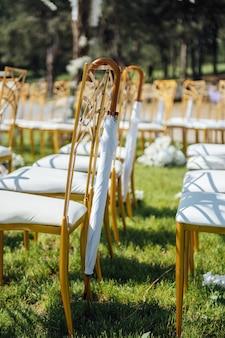 Cerimônia de casamento festiva. guarda-chuva pendurado em uma cadeira vazia.