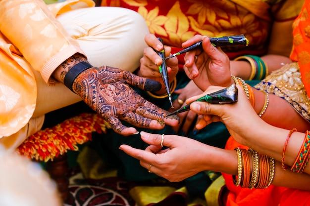 Cerimônia de casamento indiano: mão do noivo com design mehandi