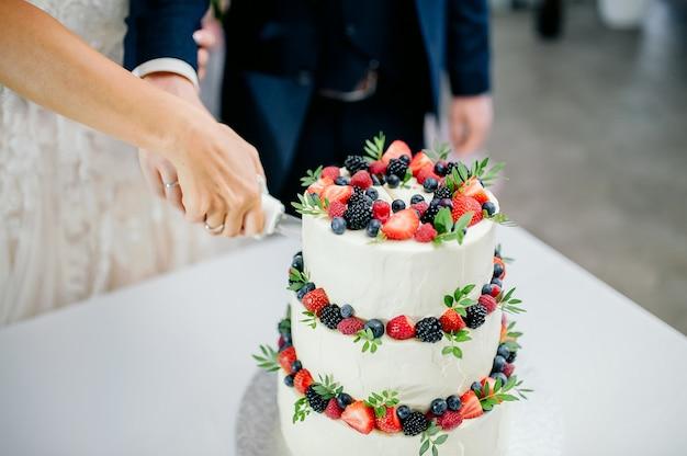 Cerimônia de casamento. mãos de noivos cortam um bolo de três camadas branco com morangos e amoras