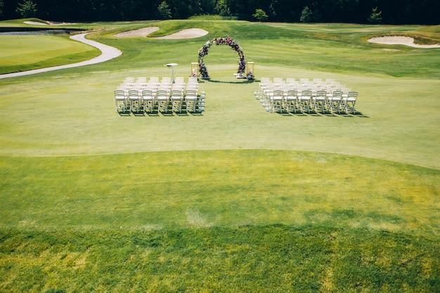 Cerimônia de casamento na natureza. fileiras de cadeiras brancas no gramado.