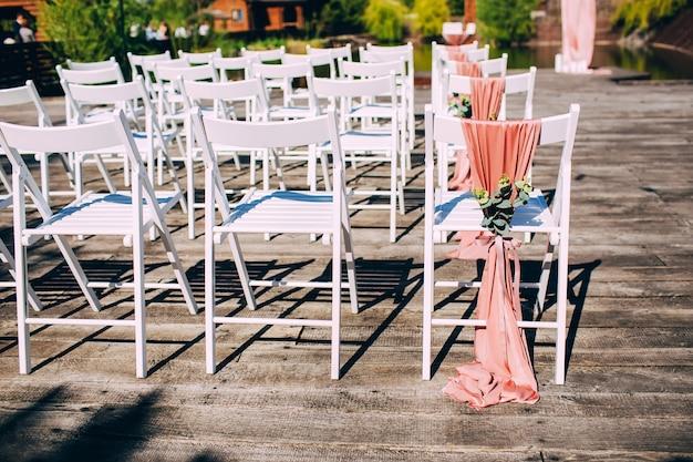Cerimônia de casamento na natureza. linhas de cadeiras de madeira brancas. tempo ensolarado.