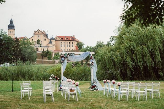 Cerimônia de casamento na rua no gramado verde. decoração com arcos de flores frescas para a cerimônia.
