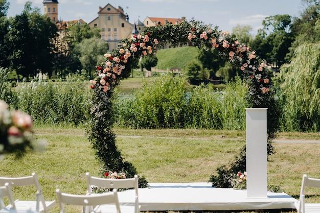 Cerimônia de casamento na rua no gramado verde perto do castelo de nesvizh.